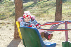 Toddler girl playing on roundabout or merry-go Stock Photos