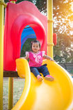 Toddler girl playing on a slide at children playground.  Stock Image