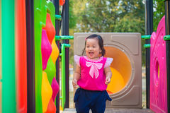 Toddler girl playing on a slide at children playground.  Stock Images