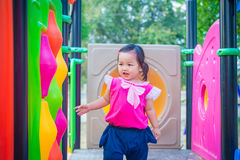 Toddler girl playing on a slide at children playground.  Stock Photos