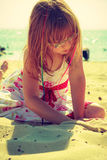 Toddler girl playing on summertime on beach Royalty Free Stock Photo