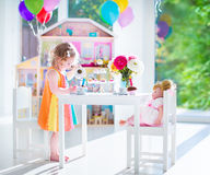 Toddler girl playing tea party with a doll. Adorable toddler girl with curly hair wearing a colorful dress on her birthday playing tea party with a doll, toy Royalty Free Stock Photos