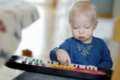Toddler girl playing toy piano Royalty Free Stock Image