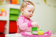 Toddler girl playing with toys. Adorable toddler girl playing with toys at home or daycare place Stock Images