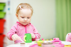 Toddler girl playing with wooden toys Royalty Free Stock Photo