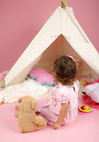 Toddler Girl Pretend Play with Teepee Tent and Stuffed Bear Toy Stock Photo
