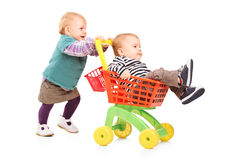 Toddler girl pushing her brother in a toy cart Royalty Free Stock Photo