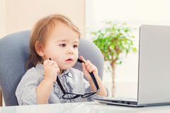 Toddler girl putting on big glasses while using her laptop Royalty Free Stock Photo