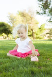 Toddler Girl Putting Coins Into Her Piggy Bank Outdoors Royalty Free Stock Image