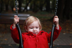 Toddler girl in red duffle coat on the playground, swinging Stock Photos