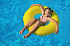 Toddler girl relaxing in swimming pool Stock Images