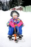 Toddler girl riding her snow scooter Stock Image