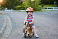 Toddler girl riding wooden tricycle on the street Stock Photo