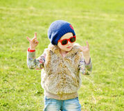 Toddler girl rock out. Cute little girl making a rock-n-roll sign outdoors Royalty Free Stock Image