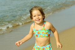 Toddler girl running at beach Stock Image