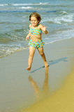 Toddler girl running at beach Stock Photography