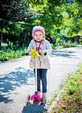 Toddler girl on a scooter in a park Royalty Free Stock Images