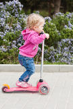 Toddler girl on a scooter in a park. In spring day Royalty Free Stock Image