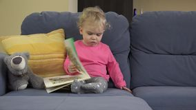 Toddler girl show various emotions when turning pages of book with images. stock video footage