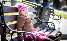 Toddler girl sitting on the bench Royalty Free Stock Photography