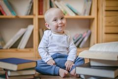 Toddler girl sitting with books in front of book shelves stock photo