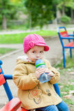 Toddler girl sitting and drinks water Stock Image