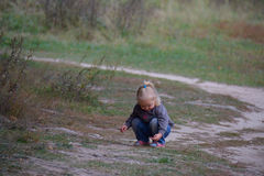 Toddler girl sitting on the forest path Royalty Free Stock Photos