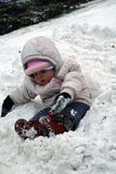 Toddler girl sitting in a heap of snow Stock Photography