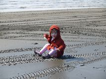 Toddler Girl Sitting in Mud. On the beach where she fell, fully clothed and wearing a hooded jacket Royalty Free Stock Photography