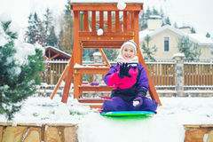 Toddler girl sitting on slade ready to play snowball fight. On playground in village at vacation. Russian winter stock images