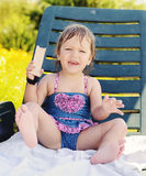 Toddler girl sitting on sun lounger Royalty Free Stock Photography