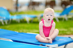 Toddler girl sitting on a sunbed by a pool Stock Image