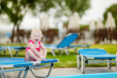 Toddler girl sitting on a sunbed by a pool Stock Photography