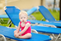 Toddler girl sitting on a sunbed by a pool Stock Photos