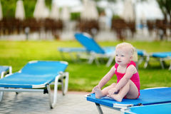 Toddler girl sitting on a sunbed by a pool Royalty Free Stock Photos