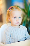 Toddler girl sitting at table Stock Images