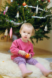 Toddler girl sitting under the Christmas tree Stock Image