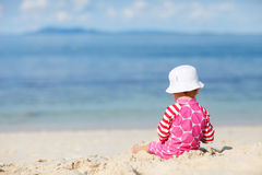 Toddler girl sitting on white sand beach Stock Photography