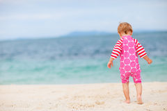 Toddler girl sitting on white sand beach Stock Photos