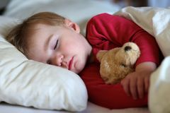 Toddler girl sleeping in bed. Healthy child, sweetest blonde toddler girl sleeping in bed holding her teddy bear Royalty Free Stock Photos