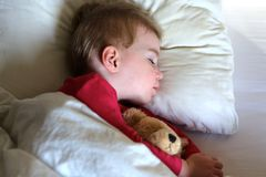 Toddler girl sleeping in bed. Healthy child, sweetest blonde toddler girl sleeping in bed holding her teddy bear Stock Photos