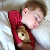 Toddler girl sleeping in bed. Healthy child, sweetest blonde toddler girl sleeping in bed holding her teddy bear Royalty Free Stock Photo