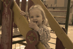 Toddler girl on the slide, with her finger in the mouth, sepia t. Toddler girl on the slide, with her finger in the mouth, smiling, sepia toned Royalty Free Stock Images