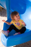 Toddler girl on slide with static electricity. Cute and happy 2 year old toddler girl at the bottom of a blue playground slide has static electricity in her hair Royalty Free Stock Photography