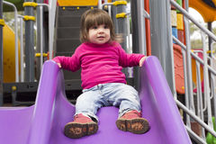 Toddler girl sliding down on slide. In playground park Royalty Free Stock Photo