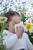 Toddler girl sneezing in a daisy flowers Royalty Free Stock Photography
