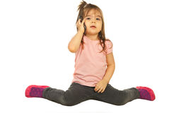 Toddler girl speaking by phone mobile. And sitting on floor isolated on white background Royalty Free Stock Photos