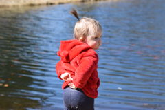 Toddler girl standing in front of pond Stock Images