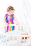 Toddler girl standing at round bed of her brother Royalty Free Stock Photography