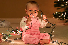 Toddler girl with string of Christmas lights Royalty Free Stock Images